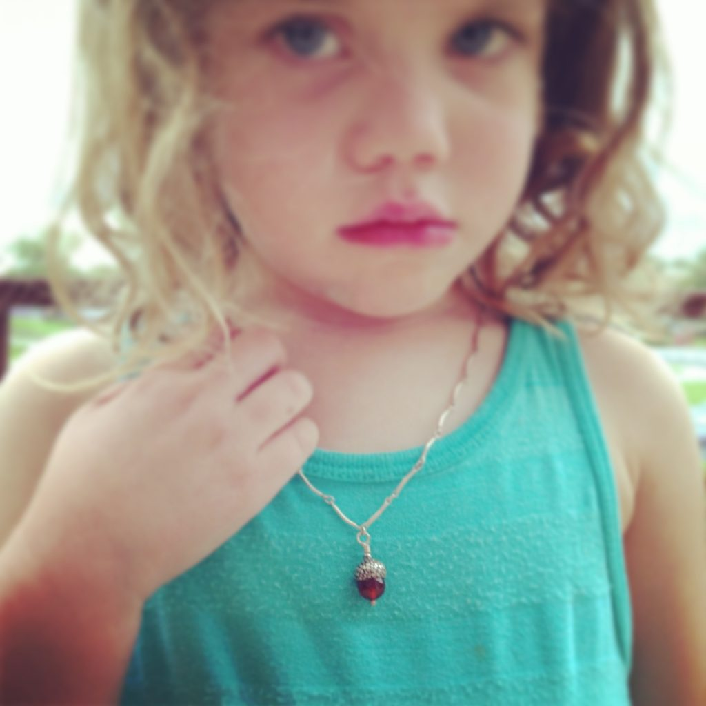 young girl wearing acorn necklace