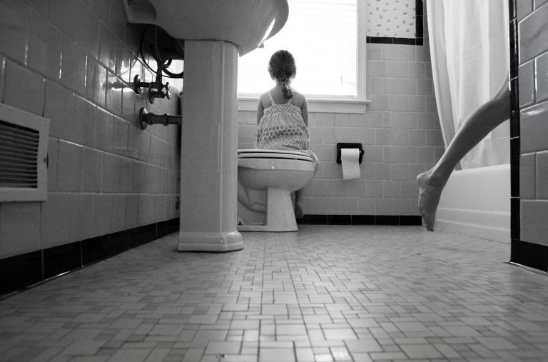 child sitting on toilet glancing outside window