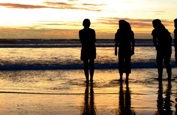 silhouette shots of four girls on the beach enjoying the dramatic sunset; new friends after big losses