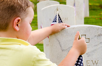 young boy visiting grave on memorial day