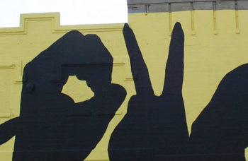 """grief mural of hand silhouettes spelling out the word """"love"""""""